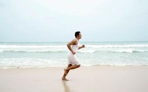 мужчина бежит по пляжу